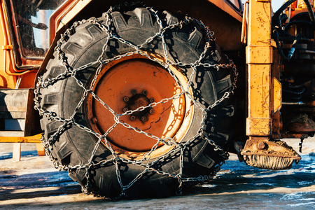 Snow chains outside of a tractor tire - winter transportation imagewinter photo