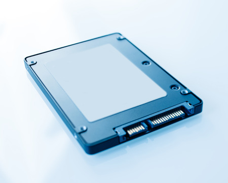 SSD disk drive in blue technological background - tilt-shift lens used to accent the center of the hdd and to emphasize the attention its connections photo