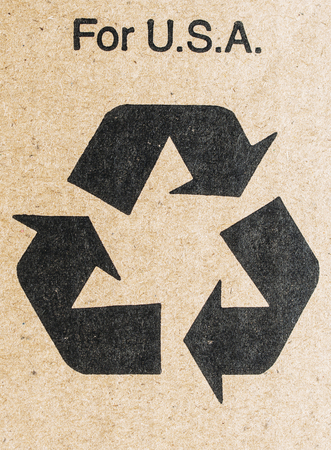 Recycle for USA - recycle sign isolated on cardboard with the text for USA above photo