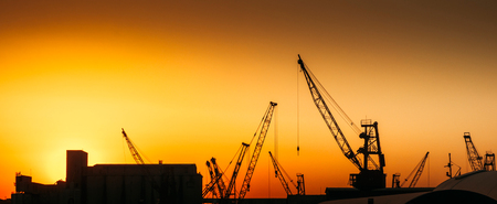 maneuverable: Construction cranes on industry production site with warm sunset on background