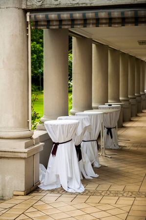 Wedding or party venue preparation with covered bar tables in a luxury ancient corridor photo