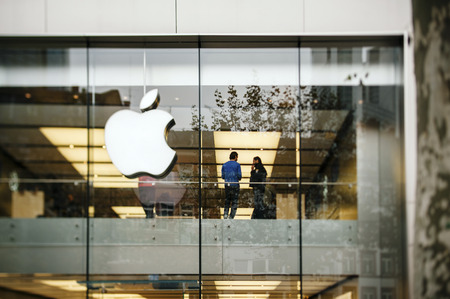 FRANKFURT AM MAIN, GERMANY - NOVEMBER 12, 2012: Apple Store logo and facade with Genius Employee explaining to a customer about the latest launched iPad Tablet.Apple is the world's largest publicly traded company wich sells consumer electronics and innova Editoriali