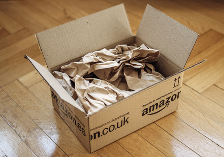 LONDON, UNITED KINGDOM - MARCH 05, 2014: Opened Amazon.co.uk shipping package parcel box on wooden floor with protection paper inside. Amazon.com went online in 1995 and is now the largest online retailer in the world.