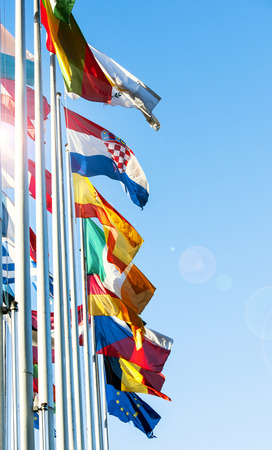 EU members flags waving in front of the European Parliament building in Strasbourg, France - vertical shot with beautiful sun flare photo
