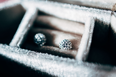 Pair of blue diamond crystal earrings in luxurt storage box - beautiful jewelry - tilt-shift lens used to outline the object and to emphasize the attention on them photo