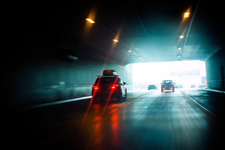 Speeding car inside a highway tunnel exiting to white calm light photo