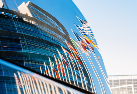 STRASBOURG, FRANCE - JANUARY 28, 2014: European flags and building of the European Parliament reflected in a car windshield parked near to the building.