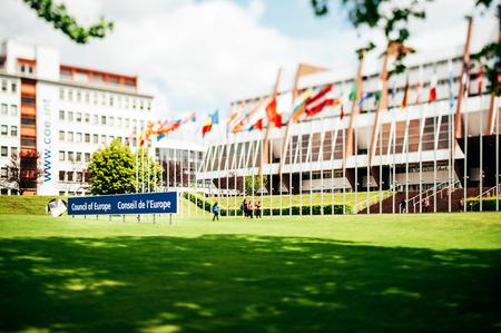 parlamentario: ESTRASBURGO, Francia - el 01 de junio 2012: Edificio de la Asamblea Parlamentaria del Consejo de Europa con banderas y fotografiar tur�stico cerca de ellos en 01 de junio 2012 de la lente Tilt-shift utilizado para nombre mejor acento de la instituci�n. Editorial