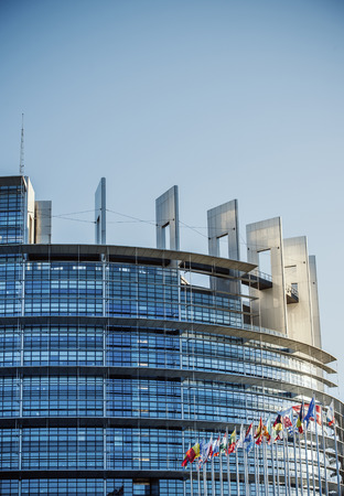 STRASBOURG, FRANCE - JAUARY 28, 2014:  Seat of the European Parliament in Strasbourg, France with all European members countries flags as seen on sunset on January 28, 2014. The institution is legally bound to meet there twelve sessions a year lasting abo