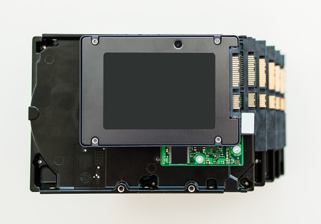ssd: Fast SSD disk  solid state drive  placed over a stack of older 3 5 HDD