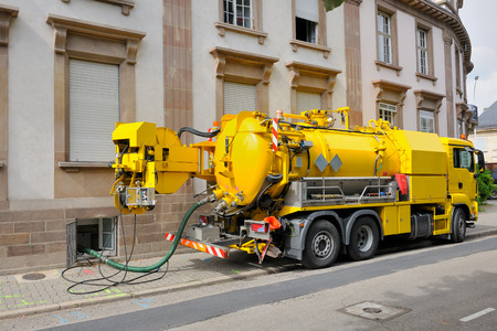 overflows: Sewage - sewerage - truck on city street in working process to clean up sewerage overflows, cleaning pipelines and potential pollution issues from an modern building. This type of truck is used for residential septic systems or commercial sewage systems