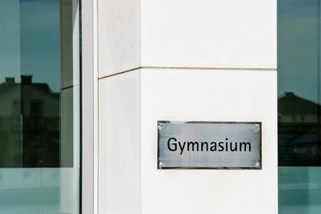 voortgezet onderwijs: Gymnasium school teken op een marmeren muur naast de ingang van een studie-omgeving die hoger middelbaar onderwijs biedt