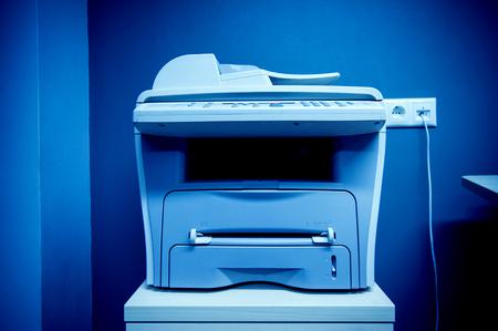 impresora: Impresora Oficina dispositivo multi-funcional en la mesa enchufado en un puerto de comunicaciones en una pared
