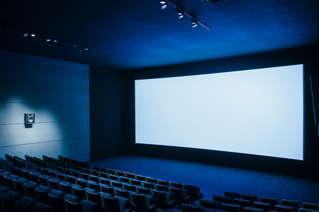 Cinema auditorium with white screen and luxury seats - dark movie theatre ready for projection