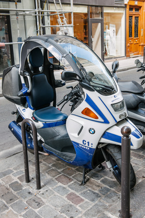 afflatus: PARIS, FRANCE - AUGUST 18, 2014: BMW C1 200 scooter parked on a pedestrian area in a city street. BMW C1 is the rare enclosed scooter manufactured by Bertone for BMW and features most innovative design and emphasis on safety.