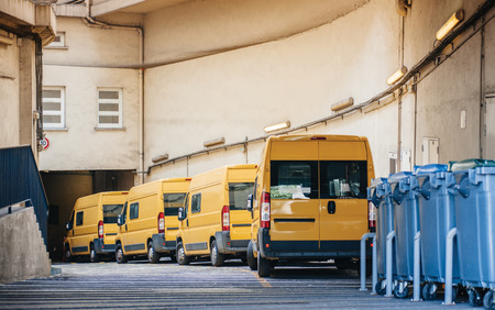 Row of yellow delivery and service van, trucks and cars in front of the entrance of a warehouse distribution logistic plant