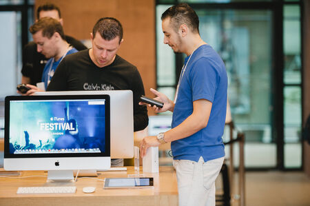 STRASBOURG, FRANCE - SEPTEMBER 19, 2014: An Apple Inc. genius employee assists a customer with the purchase during the sales launch of the iPhone 6 and iPhone 6 Plus at the companys Place Kleber store in France. Thousands of people waited next to Apple S