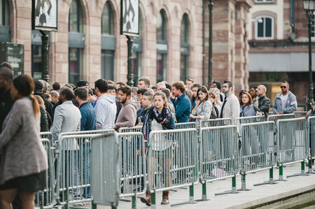 STRASBOURG, FRANCE - SEPTEMBER 19, 2014: A woman leaving the long waiting line outside the Apple Inc. store during the sales launch of the iPhone 6 and iPhone 6 Plus in Europe, on Friday, Sept. 19, 2014. Apple stores attracted long lines of fans and shopp