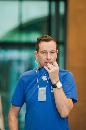 waited: STRASBOURG, FRANCE - SEPTEMBER 19, 2014: A sales assistant talking via walkie-talkie in Apple Store just before the sales of the new smart phone on September 19, 2014. Thousands of people waited next to Apple Store worldwide to be among the first people t