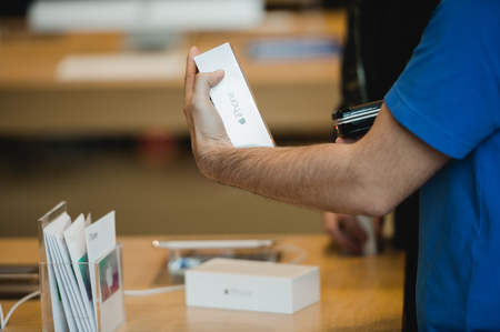 STRASBOURG, FRANCE - SEPTEMBER 19, 2014: A sales assistant scans new Apple iPhone 6 phones at the Apple Store on the first day of sales of the new smart phone on September 19, 2014. Thousands of people waited next to Apple Store worldwide to be among the