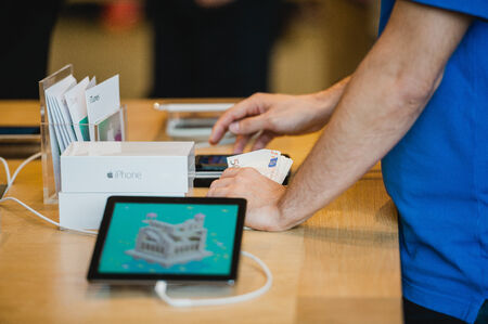 manufacturer: STRASBOURG, FRANCE - SEPTEMBER 19, 2014: An Apple Inc. genius employee assisting a customer with the purchase during the sales launch of the iPhone 6 and iPhone 6 Plus at the companys Place Kleber store in France. Thousands of people waited next to Apple