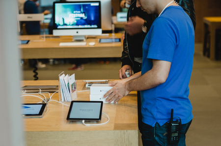 waited: STRASBOURG, FRANCE - SEPTEMBER 19, 2014: An Apple Inc. genius employee assists a customer with the purchase during the sales launch of the iPhone 6 and iPhone 6 Plus at the companys Place Kleber store in France. Thousands of people waited next to Apple S