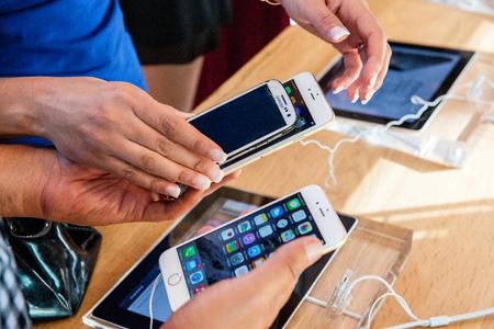 manzana: Par�s, Francia - 20 de septiembre 2014: Amigos que comparan el nuevo iPhone de Apple y el iPhone 6 6 Plus con un Samsung m�s viejo destruido durante el lanzamiento de ventas de los �ltimos smartphones de Apple Inc. en la tienda de Apple en Par�s, Francia Editorial