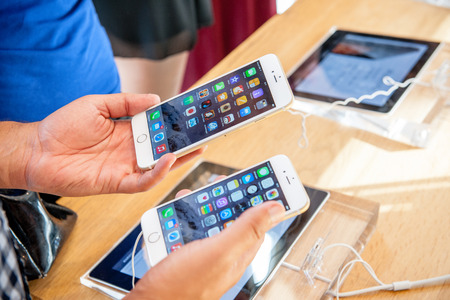 PARIS, FRANCE - SEPTEMBER 20, 2014: Man comparing the new Apple iPhone 6 and iPhone 6 Plus during the sales launch of the latest Apple Inc. smartphones at the Apple store in Paris, France Reklamní fotografie - 31703095