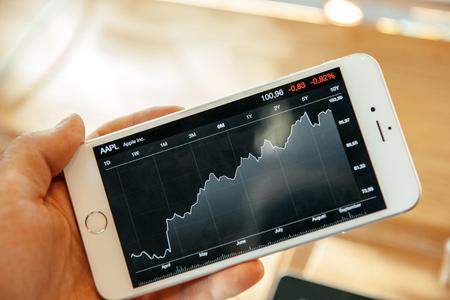manzana: PARIS, FRANCIA - 20 de septiembre 2014: Mano un iPhone 6 Plus mostrando la evoluci�n de Apple precio de las acciones en su gran pantalla durante el lanzamiento de ventas de los �ltimos smartphones de Apple Inc. en la tienda de Apple en Par�s, Francia