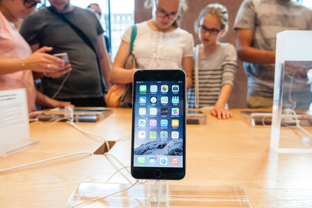 PARIS, FRANCE - SEPTEMBER 20, 2014: An iPhone 6 smartphone stands on display inside an Apple Store with a mother and her daughter admiring other iPhone 6