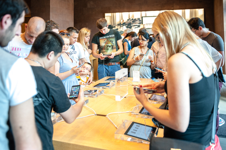 PARIS, FRANCE - SEPTEMBER 20, 2014: Customers admiring the new iPhone 6 and iPhone 6 Plus at the Apple Inc. store in Paris, France