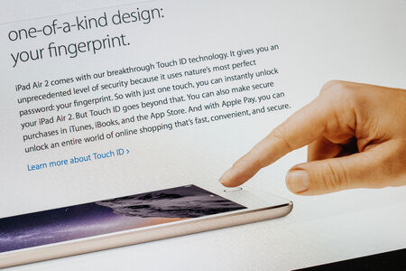 PARIS, FRANCE - 17 OCTOBER 2014: Photo of Apple iPad tablet with apple.com webpage of the new iPad Air 2 and iPad Mini 3 featuring fingerprint security button. Apple unveiled the new iMac iPad Air 2 and iPad Mini 3 on 16 Oct