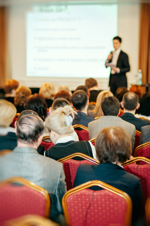 Business conference speaker with presentation speaking to mixed age team people audience