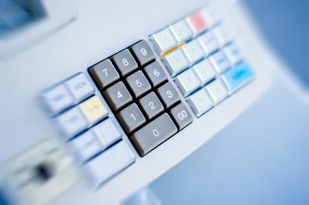 Cash register buttons on blue background photo