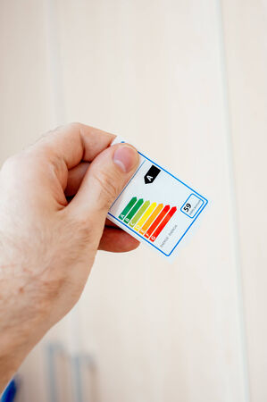 Energy efficiency label sticker used for household appliances and electrical devices in man hand photo