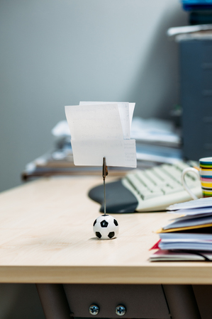 Beautiful note memo holder in form of soccer ball with memo on business office table photo