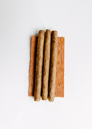 Three cigarillos on tobacco leaf on white background photo