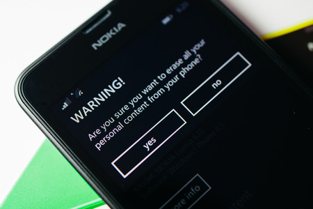 microsoft: LONDON, UNITED KINGDOM - NOVEMBER 9, 2014: Nokia Lumia smartphonewith Warning message on screen display. Microsoft has announced that it will stop using Nokia branding on all future mobile phones