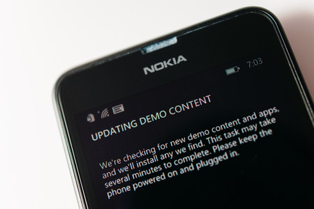 microsoft: LONDON, UNITED KINGDOM - NOVEMBER 9, 2014: Nokia Lumia smartphone -windowsphone with Updating Demop Content message on screen. Microsoft has announced that it will stop using Nokia branding on all future mobile phones Editorial