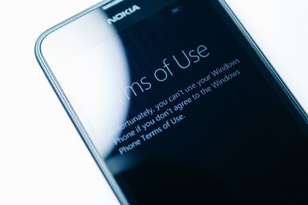 microsoft: LONDON, UNITED KINGDOM - NOVEMBER 9, 2014: Nokia Lumia smartphone windowsphone featuring Terms Of Use on touchscreen display. Microsoft has announced that it will stop using Nokia branding on all future mobile phones Editorial