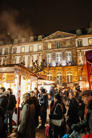 chalets: STRASBOURG, FRANCE - DEC 5, 2014: Strasbourg City Hall seen through Christmas Market visitors and chalets. Strasbourg is considered the most picturesque experience of Christmas spirit and one of the oldest Christmas Market in Europe attracting over 2 mill