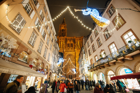 public market: STRASBOURG, FRANCE - DEC 5, 2014: Notre-Dame de Strasbourg Cathedral main street square decorated for Christmas. Strasbourg is considered the most picturesque experience of Christmas spirit and one of the oldest Christmas Market in Europe attracting over
