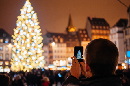 STRASBOURG, FRANCE - DEC 5, 2014: Man photographing on smartphone Strasbourg Christmas tree. Strasbourg is considered the most picturesque experience of Christmas spirit and one of the oldest Christmas Market in Europe attracting over 2 million visitors e