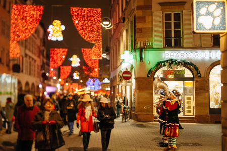 STRASBOURG, FRANCE - DEC 5, 2014: Musicians dressed like Santa playing on the street of Strasbourg. Strasbourg is considered the most picturesque experience of Christmas spirit and one of the oldest Christmas Market in Europe attracting over 2 million vis