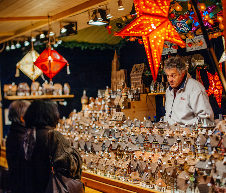 STRASBOURG, FRANCE - DEC 5, 2014: Visitors admiring souvenirs at Strasbourg Christmas Market. Strasbourg is considered the most picturesque experience of Christmas spirit and one of the oldest Christmas Market in Europe attracting over 2 million visitors
