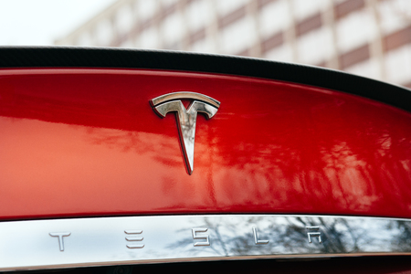 PARIS, FRANCE - NOVEMBER 29: Tesla Model S signage of a red car at Paris showroom, France. Tesla is an American company that designs, manufactures, and sells electric cars Editoriali