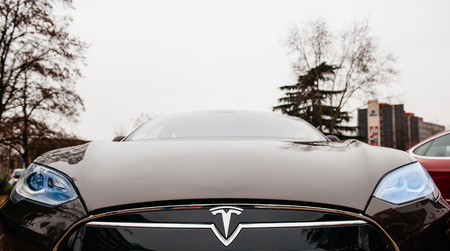 PARIS, FRANCE - NOVEMBER 29:  The Tesla Motors Inc. frontal view of badge head-lights and logo are seen below the hood of the Model S electric vehicle displayed at the companys showroom in Paris, France Редакционное