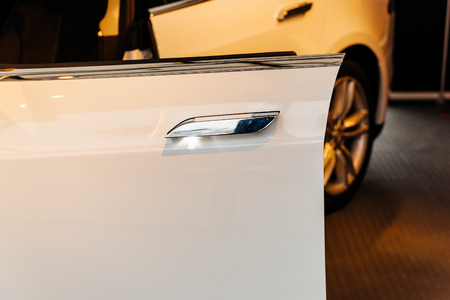 doorhandle: PARIS, FRANCE - NOVEMBER 29: Tesla Model S white car inside showroom with open door an led door-handle illumination spot. Tesla is an American company that designs, manufactures, and sells electric cars Editorial