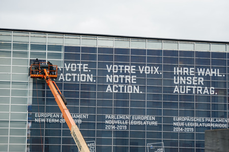 european parliament: STRASBOURF, FRANCE - JAN. 8, 2015: Workers removing old socila advertising on European PArliament depicting Your Vote, Your Action slogan
