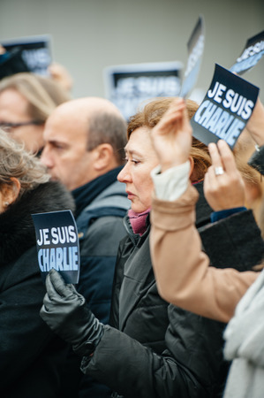 satirical: STRASBOURG, FRANCE - JANUARY 09, 2015: Council of Europe employees holding JE SUIS CHARLIE poster during a silent vigil to condemn the gun attack at French satirical magazine Charlie Hebdo office in Paris, which killed 12 people on January 7, 2015